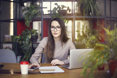 Beautiful girl wearing eye glasses in coworking studio. Using laptop and smartphone at the wooden table. Concept of young people w Royalty Free Stock Image
