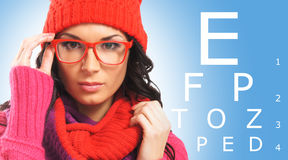 Beautiful girl wearing glasses checking her eyes Royalty Free Stock Images