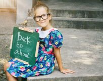 Beautiful girl wearing glasses holding chalkboard with words back to school. Outdoor portrait Stock Photo
