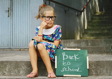 Beautiful girl wearing glasses holding chalkboard with words back to school. Outdoor portrait Stock Photography