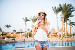 Beautiful girl wearing hat being happy use smart phone on outdoor with pool Stock Images