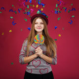 Beautiful girl wearing hat holding big striped lollipop Stock Images