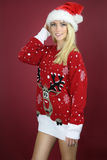 Beautiful girl wearing a kitsch Christmas sweater. Over a red background stock image