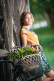 Beautiful girl wearing a nice dress with college look having fun in park with bicycle carrying a beautiful basket. Vintage scenery Stock Photography