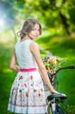 Beautiful girl wearing a nice white dress having fun in park with bicycle. Healthy outdoor lifestyle concept. Vintage scenery Stock Images