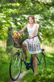 Beautiful girl wearing a nice white dress having fun in park with bicycle. Healthy outdoor lifestyle concept. Vintage scenery Stock Photos
