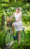 Beautiful girl wearing a nice white dress having fun in park with bicycle. Healthy outdoor lifestyle concept. Vintage scenery. Pretty blonde girl with retro Stock Photos