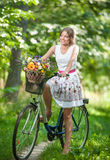 Beautiful girl wearing a nice white dress having fun in park with bicycle. Healthy outdoor lifestyle concept. Vintage scenery. Pretty blonde girl with retro Royalty Free Stock Photo