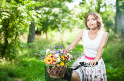 Beautiful girl wearing a nice white dress having fun in park with bicycle. Healthy outdoor lifestyle concept. Vintage scenery Royalty Free Stock Photography