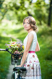 Beautiful girl wearing a nice white dress having fun in park with bicycle. Healthy outdoor lifestyle concept. Vintage scenery Royalty Free Stock Images