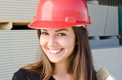 Beautiful girl wearing a red safety helmet. Royalty Free Stock Photo