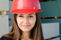 Beautiful girl wearing a red safety helmet, smiling. Royalty Free Stock Image