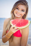 Beautiful girl is wearing red swimsuit eating Stock Photos