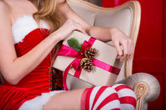 Beautiful girl wearing santa claus clothes with christmas gift in hand. Xmas concept Stock Photo