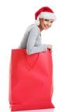 Beautiful girl wearing santa hat in red shopping bag. Stock Photos