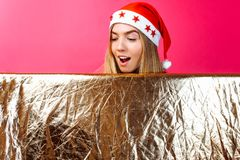 A beautiful girl wearing a Santa hat and with tinsel on her neck, the girl is holding an empty Golden colored Billboard, on a red stock photos