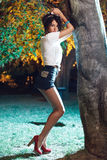 Beautiful girl wearing short pants and red heels waiting. Next to a tree Royalty Free Stock Photos