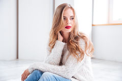Beautiful girl wearing sweater and red lipstick sitting at home Stock Photos