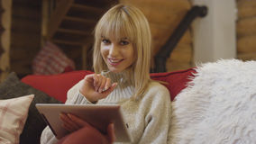 Beautiful girl wearing sweater using a tablet at home. Smiling young woman with tablet computer sitting on a couch in the living room Stock Photos
