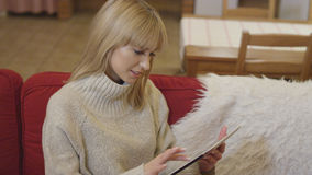 Beautiful girl wearing sweater using a tablet at home. Smiling young woman with tablet computer sitting on a couch in the living room Royalty Free Stock Photography
