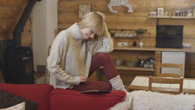 Beautiful girl wearing sweater using a tablet at home. Smiling young woman with tablet computer sitting on a couch in the living room Stock Photo