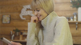Beautiful girl wearing sweater using a tablet at home. Smiling young woman with tablet computer sitting by a table in the living room Stock Photos