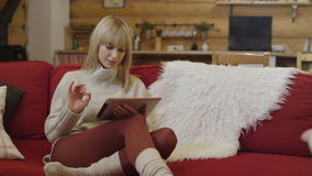 Beautiful girl wearing sweater using a tablet at home in winter. stock footage
