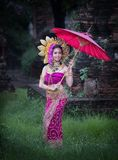 Beautiful girl wearing Thai dress and umbrella flower flow background old temple local country thailand stock image