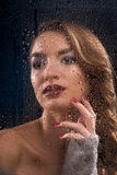Beautiful girl wearing touches wet window glass. Royalty Free Stock Photography