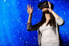 A beautiful girl wearing a virtual reality device, standing on the background of the sky. royalty free stock photography