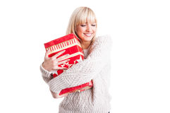 Beautiful girl wearing warm sweater hugging a present Royalty Free Stock Images