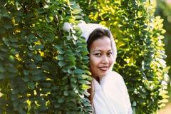Beautiful girl wearing white jacket, hiding behind the bush Royalty Free Stock Photos