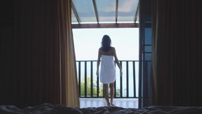 Beautiful girl is wearing white towel opens curtains and goes to sea view terrace. Young woman waking up stretches stock video footage