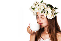 Beautiful girl wearing a wreath of jasmine and a cup of green tea. On an isolated white background Royalty Free Stock Images