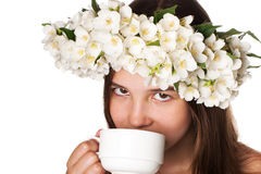 Beautiful girl wearing a wreath of jasmine and a cup of green tea. On an isolated white background Stock Photos