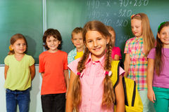 Beautiful girl wears yellow rucksack with pupils. Beautiful girl with yellow rucksack on her shoulders and other pupils behind her near the blackboard Royalty Free Stock Image