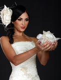 Beautiful girl in a wedding dress holding petals royalty free stock photo