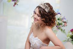 Beautiful girl in wedding dress sitting and smiling. Stock Photo