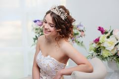 Beautiful girl in wedding dress sitting and smiling. Stock Photos
