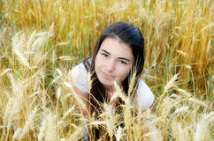 Beautiful girl in a wheat field. Beautiful girl in a field on a background of yellow and white wheat ears Royalty Free Stock Photos