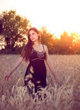 Beautiful girl in wheat field at sunset Stock Photos