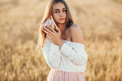 Beautiful girl in wheat field at sunset Royalty Free Stock Image