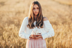 Beautiful girl in wheat field at sunset Stock Photo