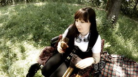 Beautiful girl in wheelchair in steampunk clothes smiling and drinking stock footage