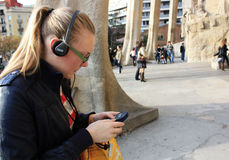 The beautiful girl whih ear-phones. Pretty blond girl listens to music on her personal stereo Stock Photography