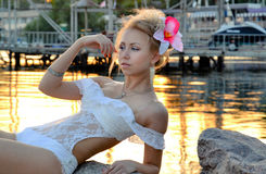 Beautiful girl in a white bathing suit. Girl in white lace bathing suit lying on the shore Stock Photos