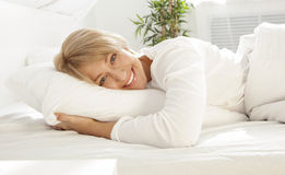 Beautiful girl in a white bed in the morning, smiling Stock Photo