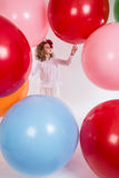 Beautiful girl in a white blouse is considering large balloons. stock image