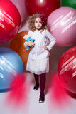 Beautiful girl in a white blouse with a soft toy comes at camera Stock Photography