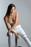 Beautiful girl in white bra and leather pants Stock Photos